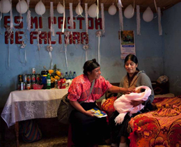 A postnatal visit by a community healthcare worker, in Nahuala, Guatemala.: While checking on the health of the newborn, she also discusses family planning with her client.