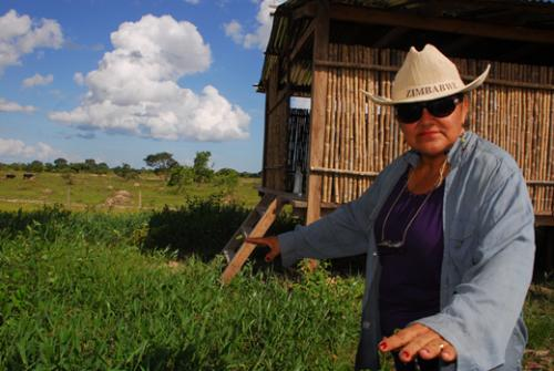 Dora Domínguez shows IPS the forage grown on the artificial hill and the feed storage shed, behind her.: This is an example of an artificial 'island' created to protect cattle and feed from annual floods in Bolivia Photograph by Franz Chávez/IPS