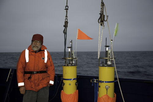 Barely visible against roiling seas: scientist Eric D'Asaro with robotic floats he developed.: Photograph courtesy of Craig Lee