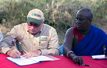 Azzedine Downes, International Fund for Animal Welfare (IFAW) President (left) and Mr. Daniel Leturesh,  representing the Maasai: sign the Kitenden Corridor certificates after they signed a lease agreement, 17 July 2013, in Amboseli National Park in Kenya. Photograph © IFAW/K. Prinsloo.