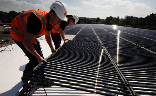 Photovoltaic solar panels being installed on the roof of Sainsbury's supermarkets.