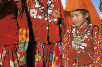 Kirghiz women in the Afghan Pamirs wear their finery, including necklaces of silver coins, at a wedding.: Photograph from Tibet Wild by George B. Schaller. Reproduced by permission of Island Press.