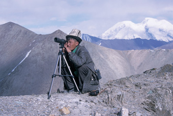 Our guide in Tajikistan scans the terrain for Marco Polo sheep. The Mustagh Ata massif across the border in China is in the: background. Photograph from Tibet Wild by George B. Schaller. Reproduced by permission of Island Press.